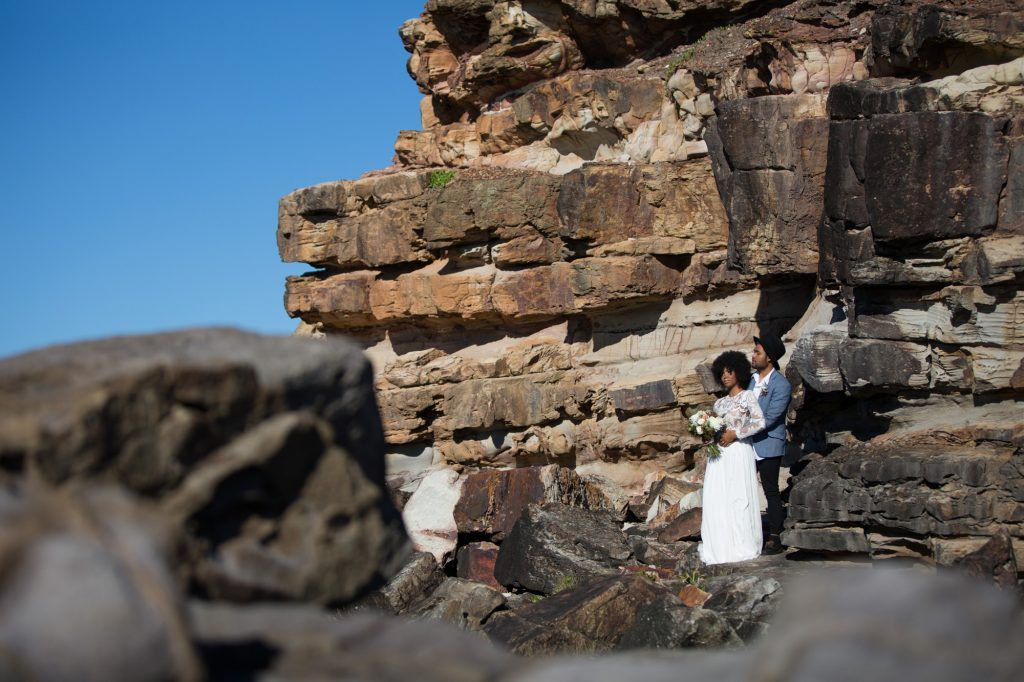 South african bride with afro and hipster groom standing together amongst a rock wall