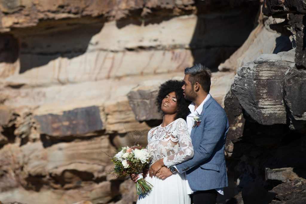 South african bride leaning back in to a man with blue hair that matches his jacket