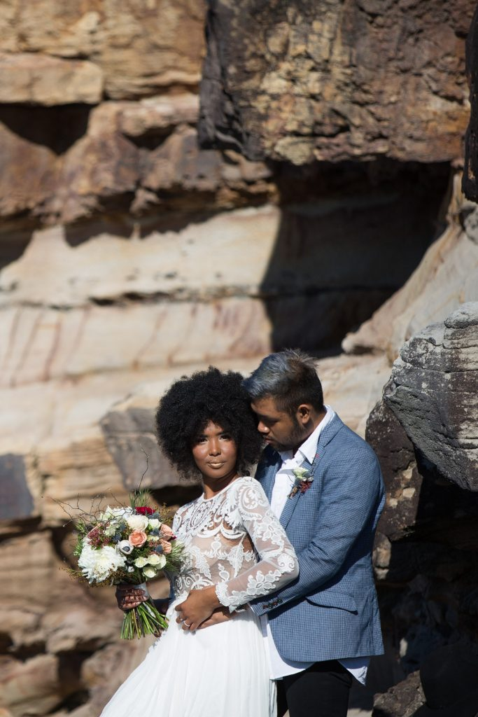 African bride with afro and lace dress, groom with blue jacket and hair standing against a rock wall