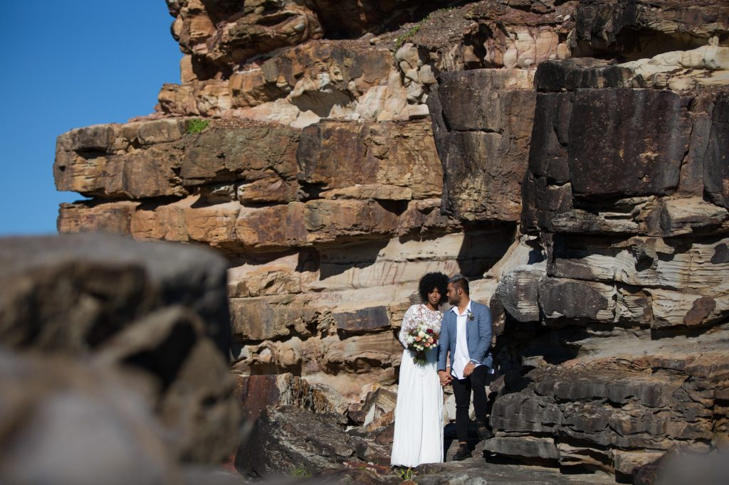 Hipster bride and groom standing against a rock wall at Point Arkwright
