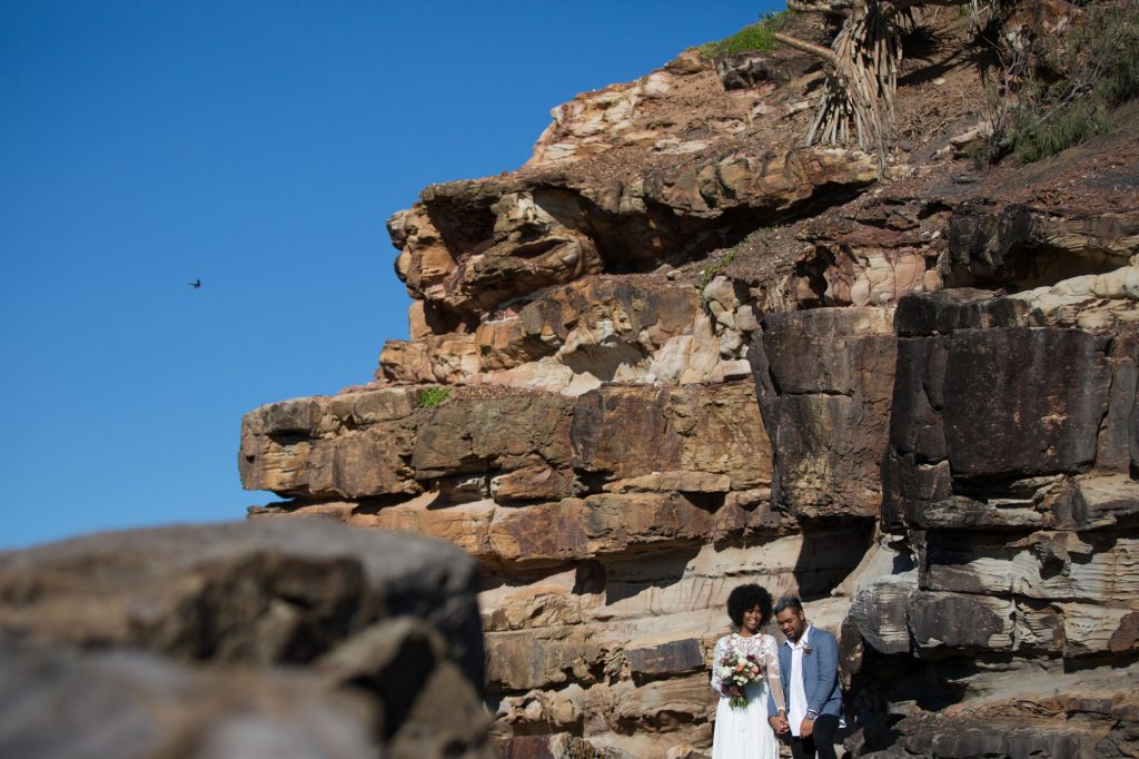 Hipster cool bride and groom laughing standing against a rock wall. Bird in the background