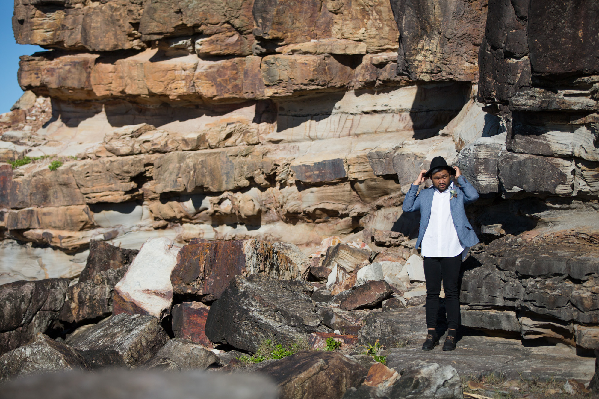 Groom standing in front of a rock wall fixing his hat