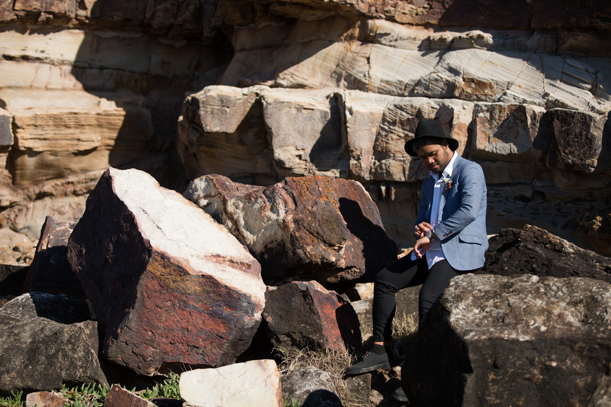 Groom wearing a hat, sitting on a rock checking his watch