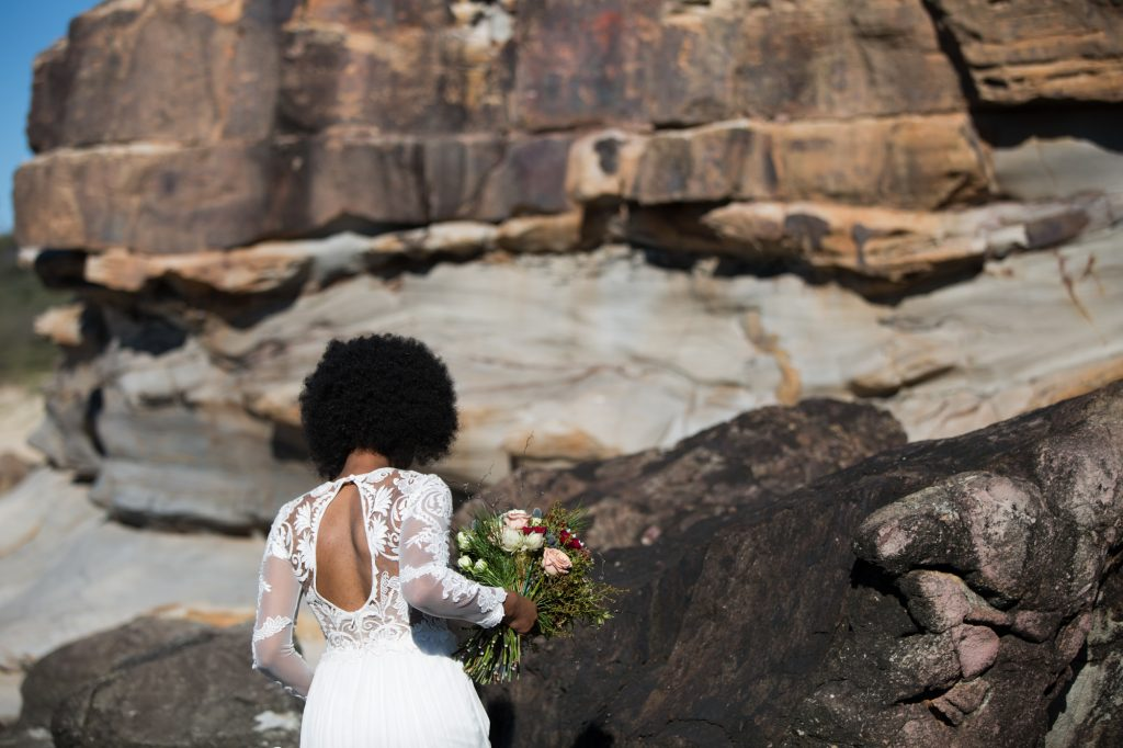 African bride with afro walks away towards rock wall, lace open back wedding dress