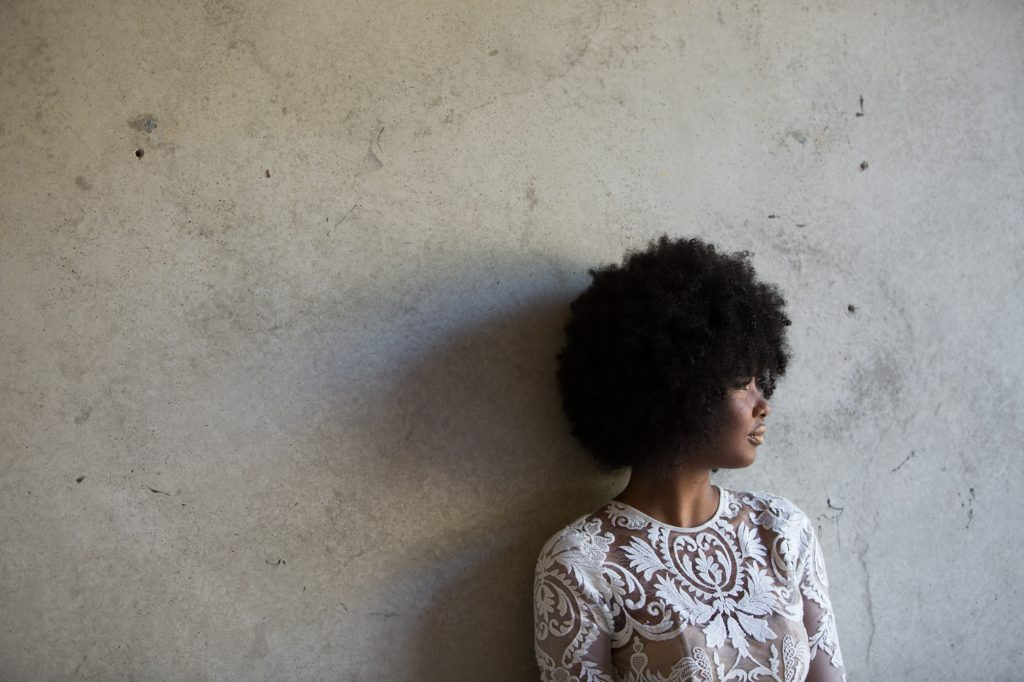 African bride with afro leaning against concrete wall