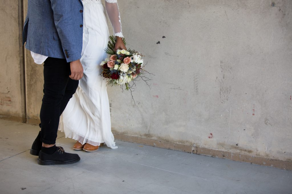 Bride and groom wearing boots and holding cool brides bouquet