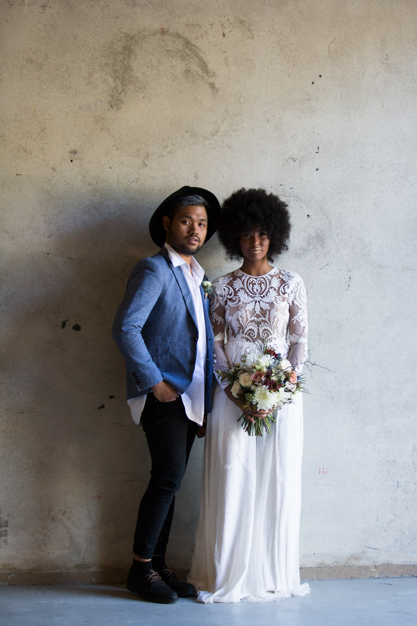 Cool bride and groom standing against brick wall