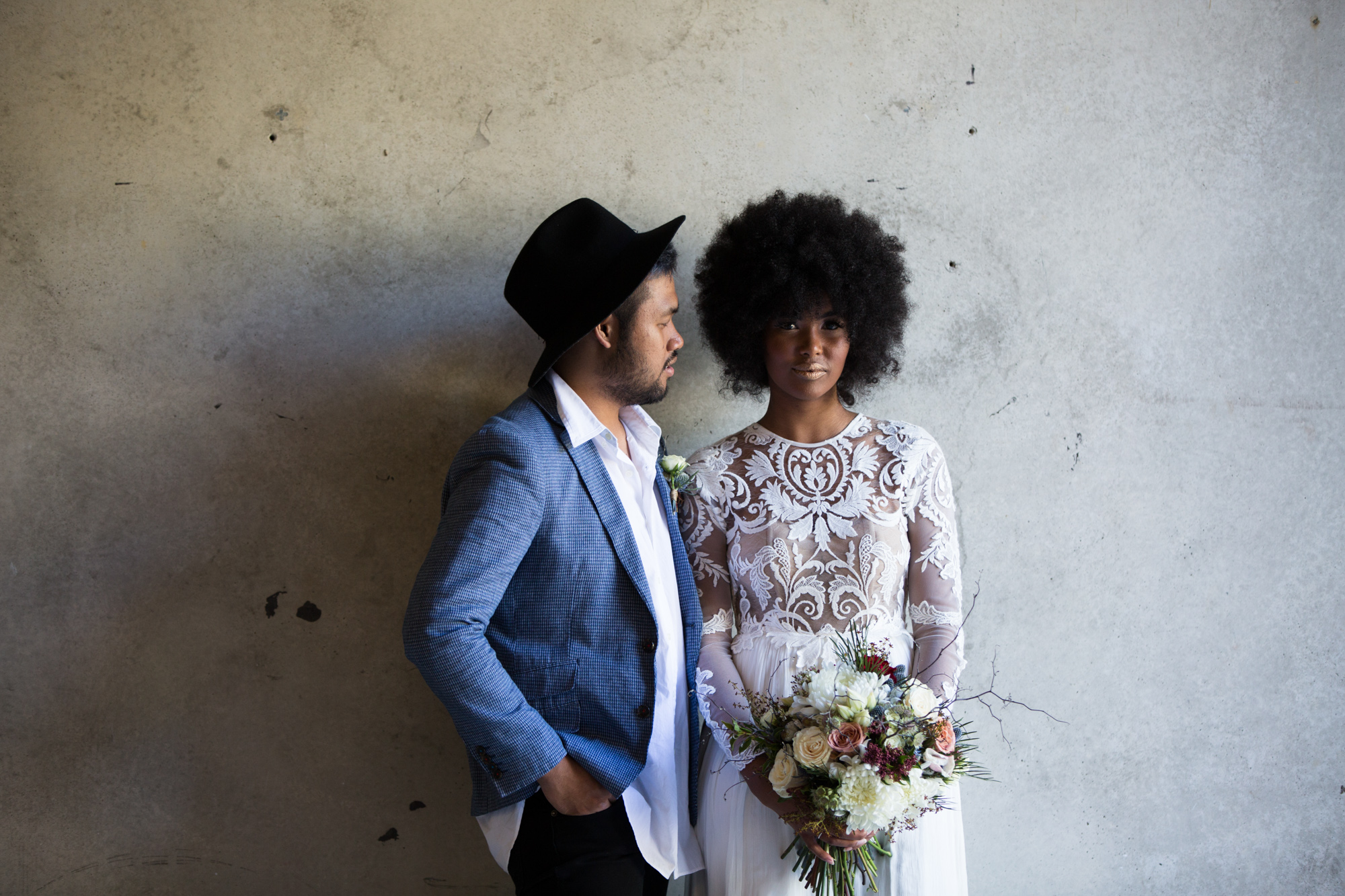 Alternative bride and groom standing against brick wall. African bride with afro wearing lace wedding dress, groom wearing blue jacket and hat