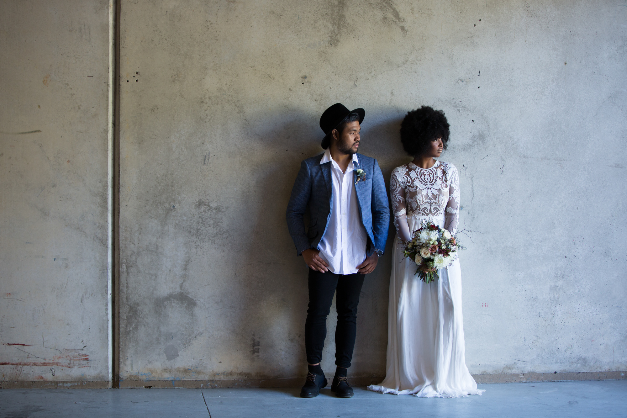 Trendy bride and groom standing against a brick wall looking off in to the distance