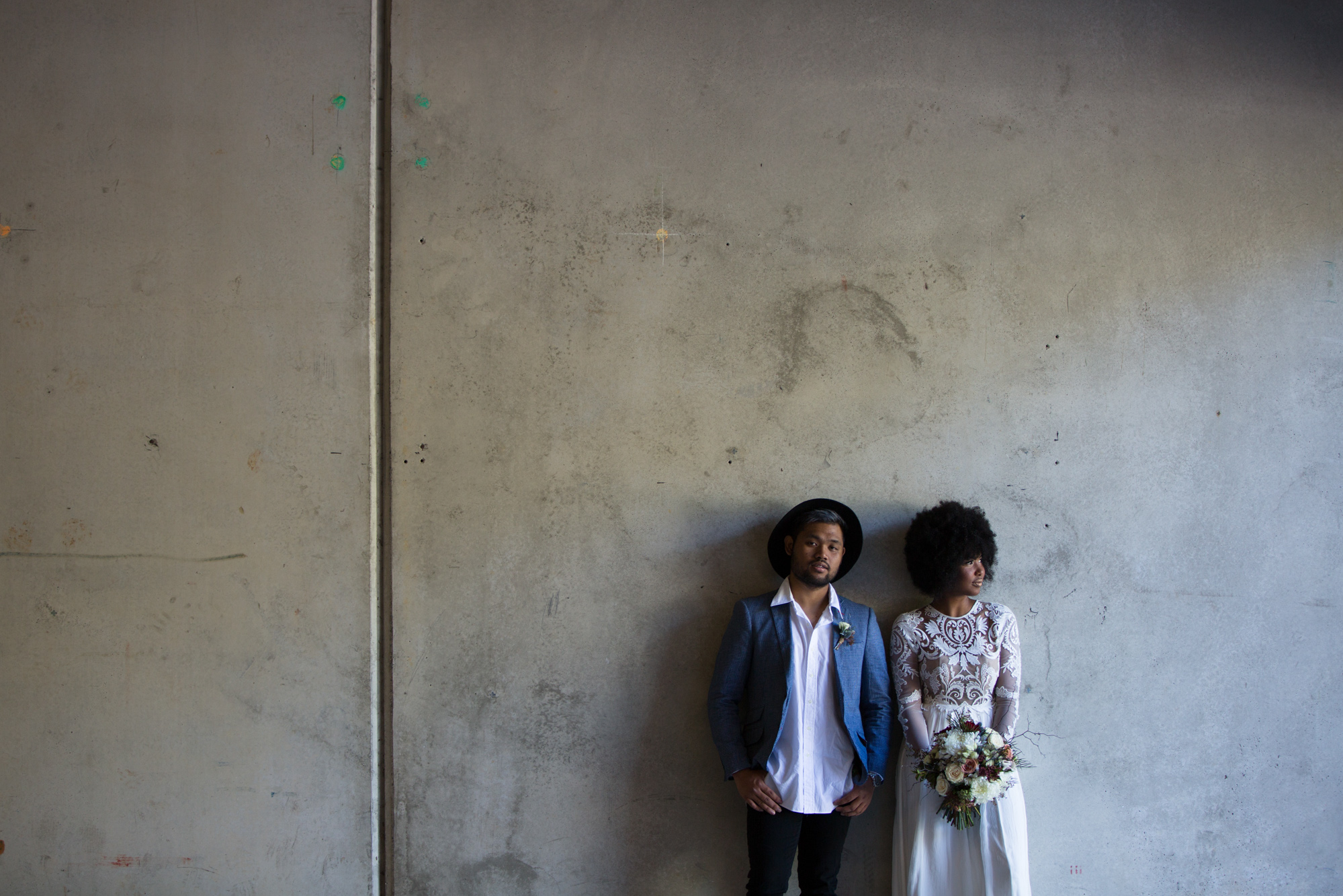 Cool bride and groom standing against brick wall. Groom wearing blue jacket and hat looking at the camera, bride wearing lace long sleeved wedding dress looking away