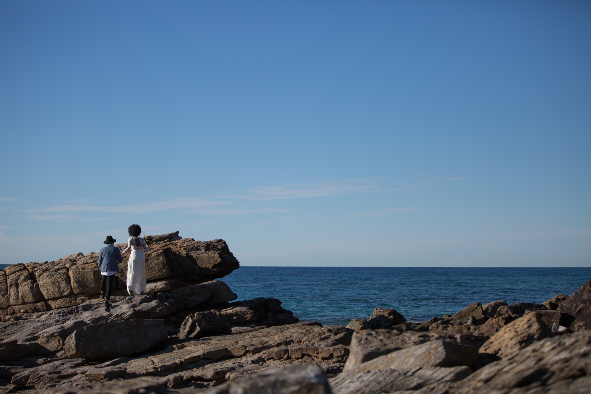 Bride and groom walking along the rocks at Point Arkwright