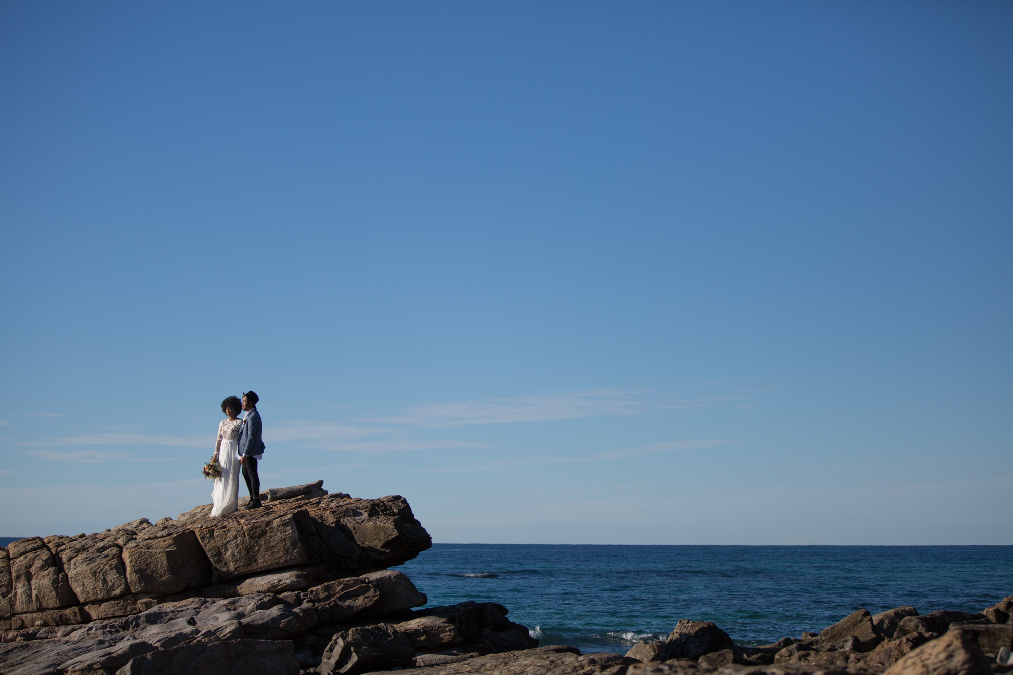 Bride and groom standing on the rocks looking off in to the distance at Point Arkwright beach