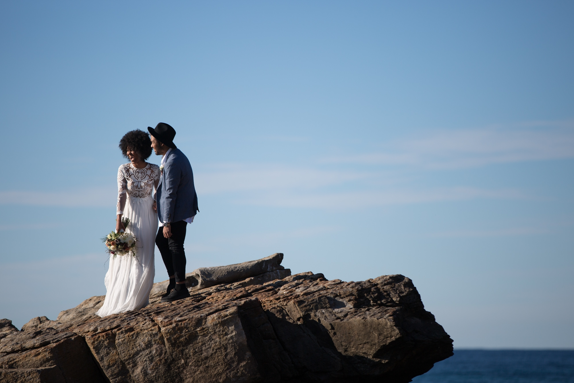 South African bride with afro and groom wearing a hat laughing on the rocks at the beach