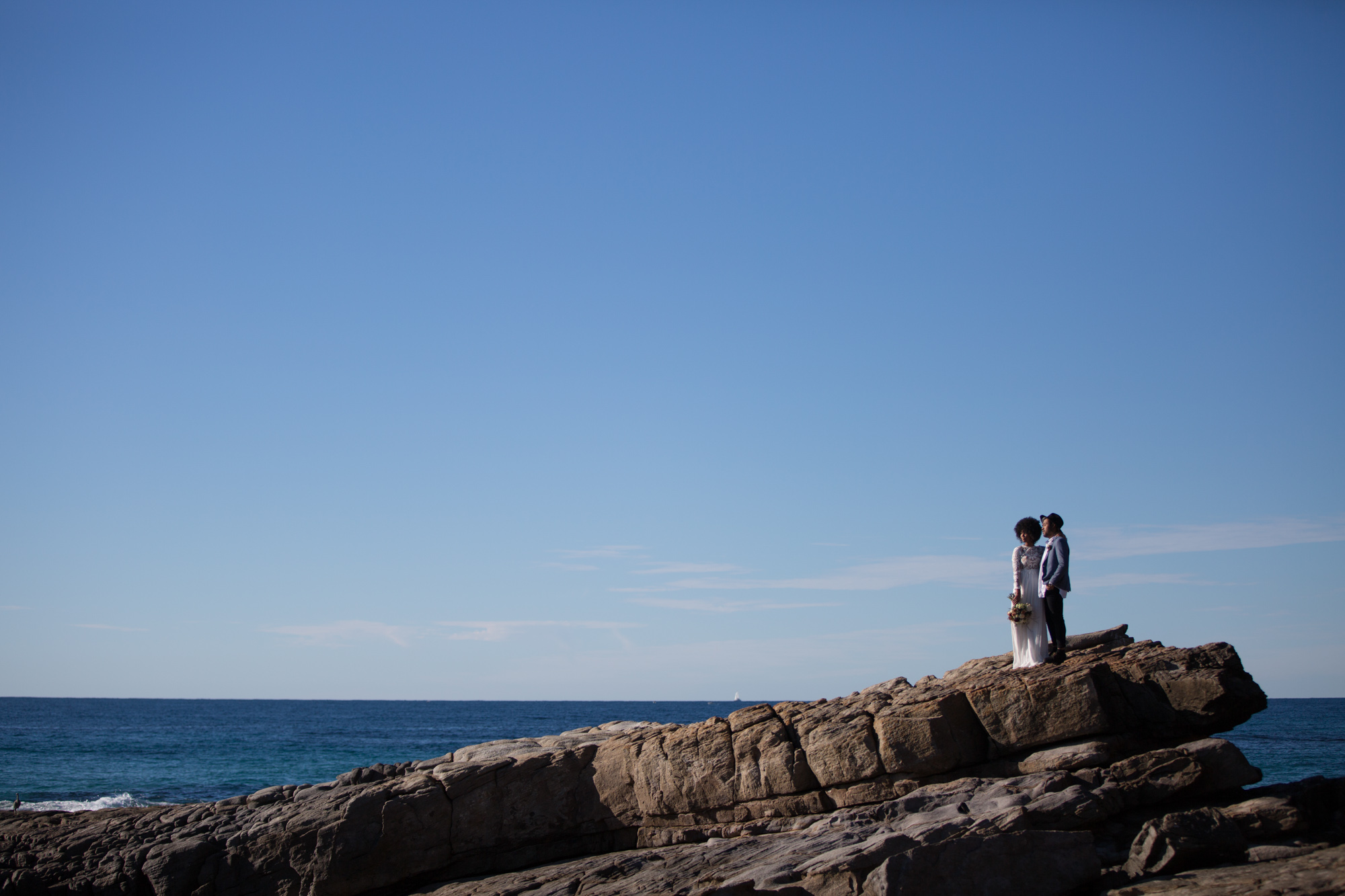 South african bride with afro and groom wearing a hat, standing on the cliff at Point Arkwright