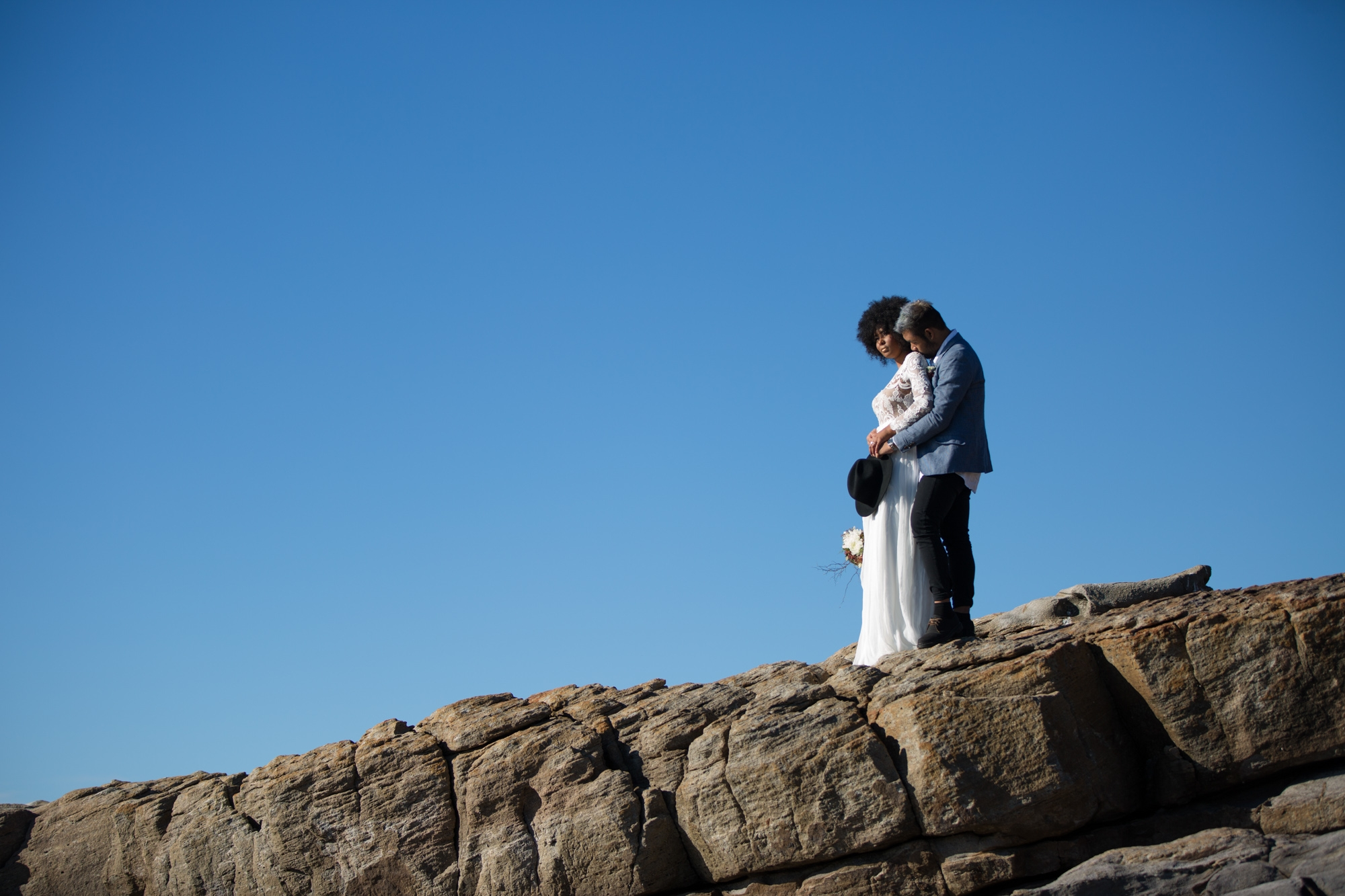 South african bride with afro wearing a lace dress. Groom with blue hair kissing her shoulder