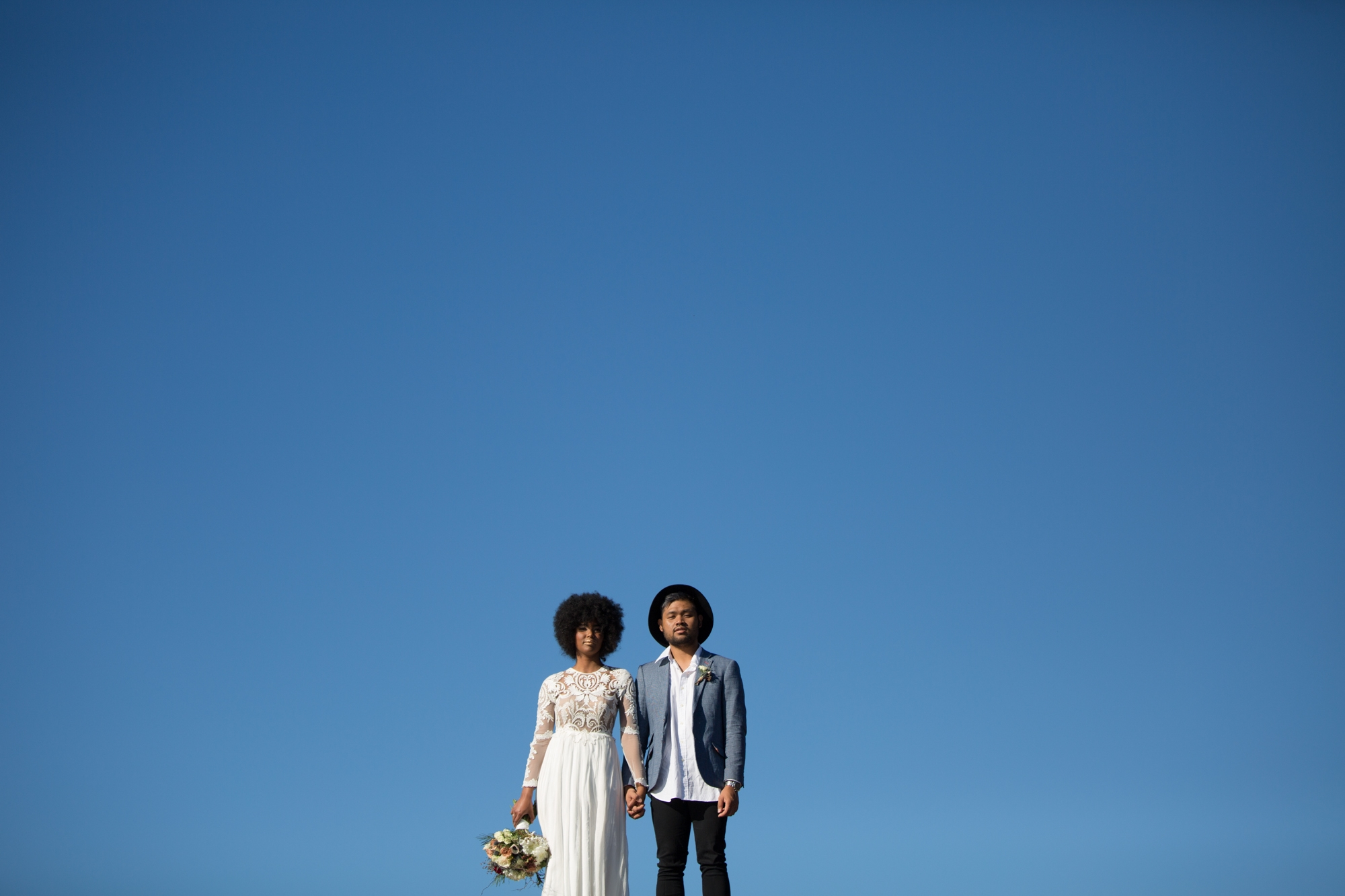 South african bride with afro, groom with hat