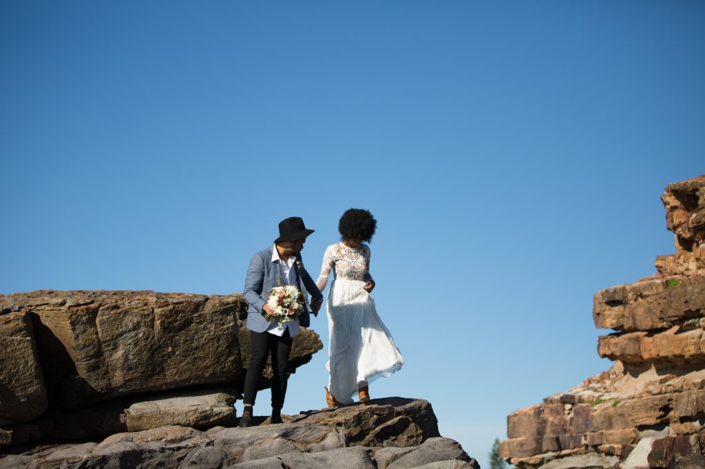 bride wearing a lace dress and boots, groom carrying her flowers and wearing a hat walk across the rocks at the beach