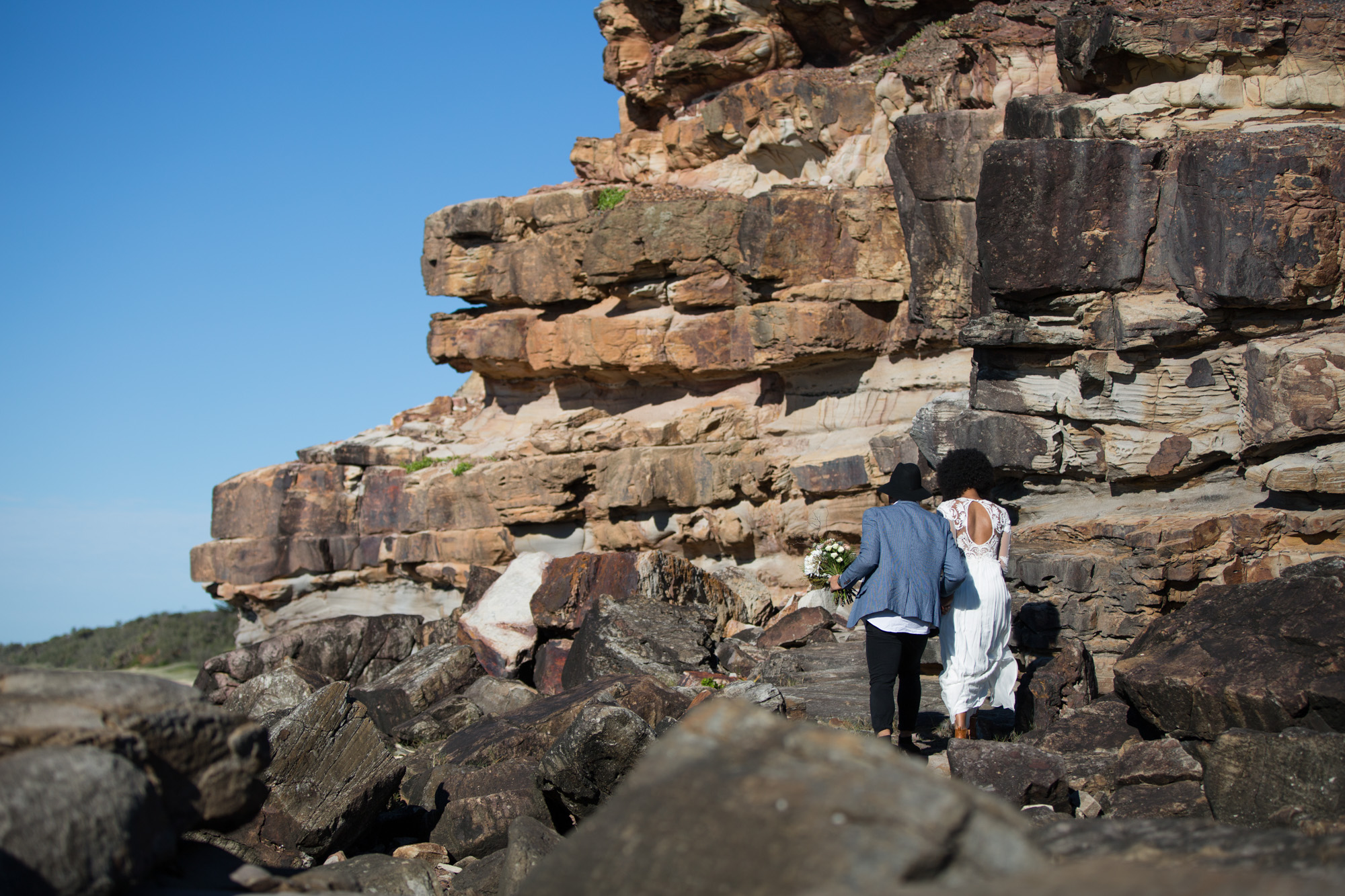 Bride and groom walking across the rocks from behind